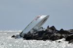 An investigator looks at a boat overturned on a jetty, Sunday, Sept. 25, 2016, off Miami Beach, Fla. Authorities said that Miami Marlins starting pitcher Jose Fernandez was one of three people killed in the boat crash early Sunday morning. Fernandez was 24. (AP Photo/Gaston De Cardenas)