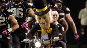 "Wake Forest's ""Demon Deacon"" mascot leads the team on the field before an NCAA college football game against Clemson in Winston-Salem, N.C., Thursday, Oct. 25, 2012. (AP Photo/Chuck Burton)"