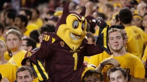 In this Nov. 16, 2013, file photo, Arizona State mascot Sparky the Sun Devil poses for students during the second half of an NCAA college football game against Oregon State in Tempe, Ariz. (AP Photo/Rick Scuteri, File)